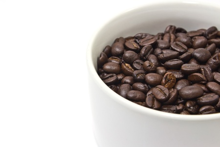 A cup and coffee beans on white background photo