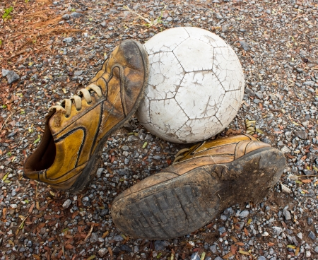 a old ball and old shoes on the ground