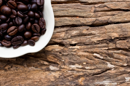 Coffee beans in white cup on wooden background  photo