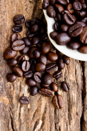 Coffee beans in white cup on wooden background. photo