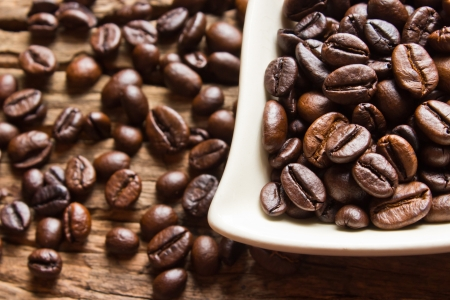 coffeetree: Fresh coffee beans and white cup  on wood