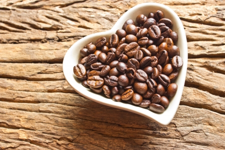 coffeetree: Fresh coffee beans in white heart cup  on wood