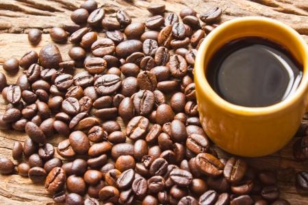 planta de cafe: Taza de caf� negro y granos de caf� sobre fondo de madera.