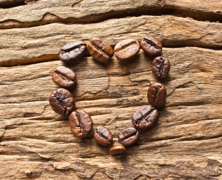 Coffee beans in a heart shape on wood photo