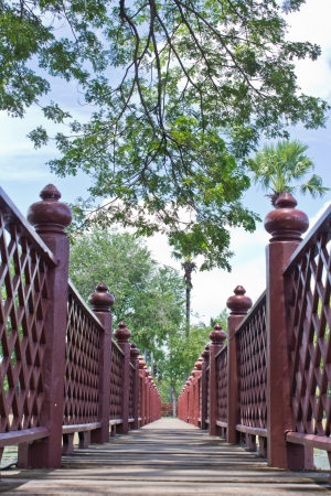 A red wooden bridge stretches across the middle photo