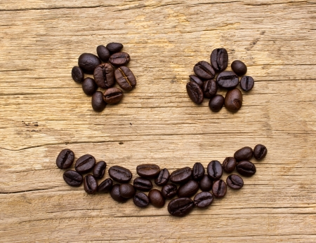 Smiling Coffee Beans on wood background photo