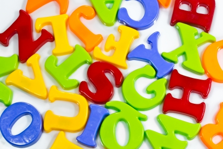 Plastic letters scattered on white background. Stock Photo