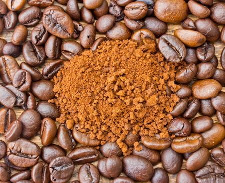 grind: Granos de caf� y granos de caf� molido en el fondo de madera Foto de archivo