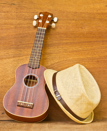 The ukulele and a hat is placed on a wooden floor. photo