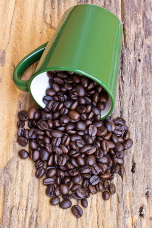 A Cup of coffee beans is on wooden board photo