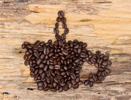 tomando refresco: taza de caf� hecha de frijoles forma de caf� sobre fondo de madera