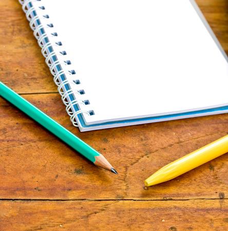 r image: l�pices y el cuaderno sobre un fondo de madera