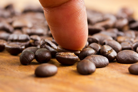 jamoke: Coffee and finger on wooden background ,Concept select coffee beans Stock Photo