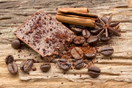 Composition of chocolate sweets, cocoa, spices and coffee bean on wooden background photo