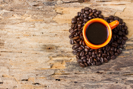 Cup of black coffee and Coffee beans arranged in heart shape on wooden background. photo