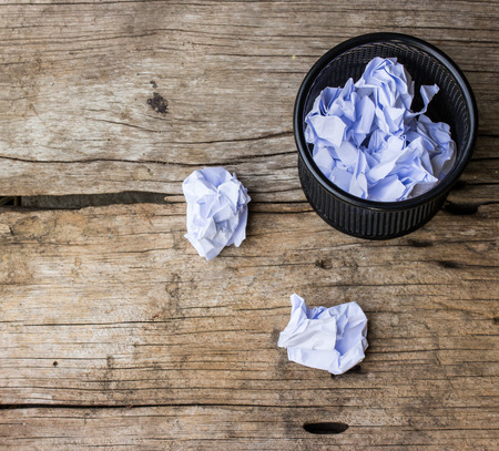 wastepaper: A lot of wrinkled paper laying in and around a wastepaper basket. Stock Photo