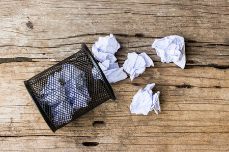 wastepaper basket: A lot of wrinkled paper laying in and around a wastepaper basket. Stock Photo