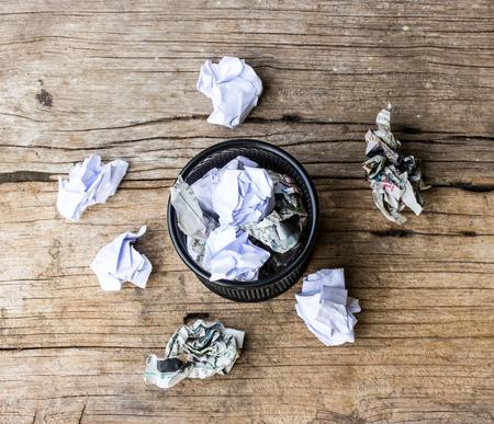 wastepaper basket: Un sacco di carta rugosa posa in ed intorno ad un cestino della carta straccia. Archivio Fotografico