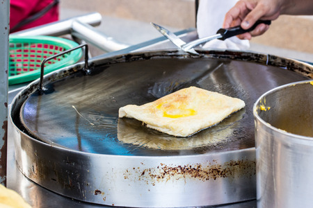 cook griddle: Making of roti snack in thailand. roti with egg or banana. fusion roti. Stock Photo
