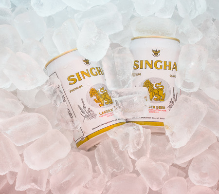 Chiang Rai, Thailand - April 14, 2015: Cans of Singha beer produced by Ale Brewery Co Ltd pictured on ice. The beer is allowed to display the Royal Garuda on the brand. Stock Photo - 38954594
