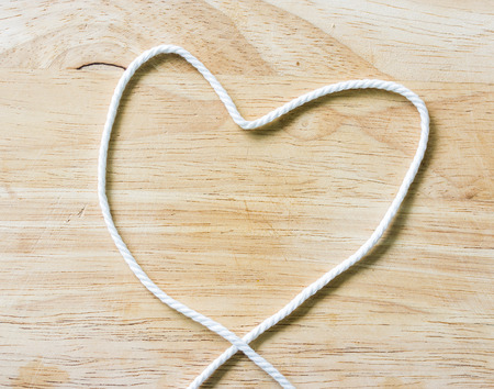 slipped: Heart Rope on a Wooden background