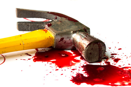 A close-up of a bloody hammer and small blood pool isolated on white.
