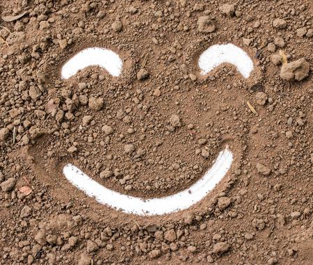 granular: Smiley face in the dirt. Stock Photo