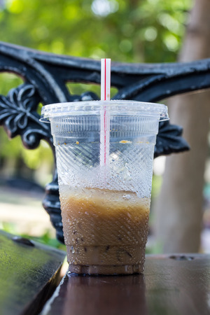 dring: Plastic coffee cup on a wood chair Stock Photo