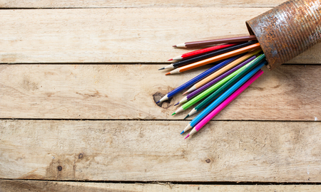 tin can: color pencils in rusty tin can, wood table