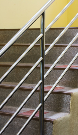 metal handrail: Interior. Brown staircase with metal railing, gray wall