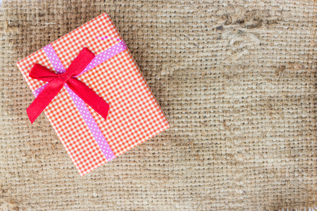 sack cloth: Small gift box on sack cloth background