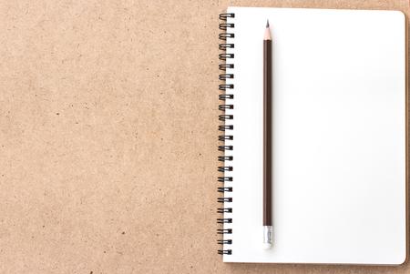 鉛筆とウッドの背景に小さなメモ帳を開く 写真素材