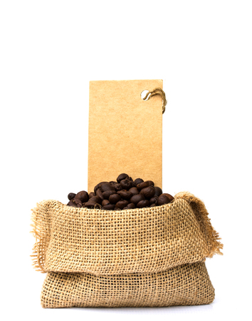 stimulant: roasted coffee beans spilled on pile and in burlap sacks and Price tag  over white background. Stock Photo