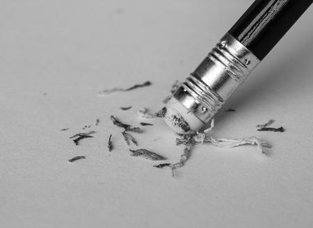 Une gomme à crayon enlever une erreur écrit sur un morceau de papier.