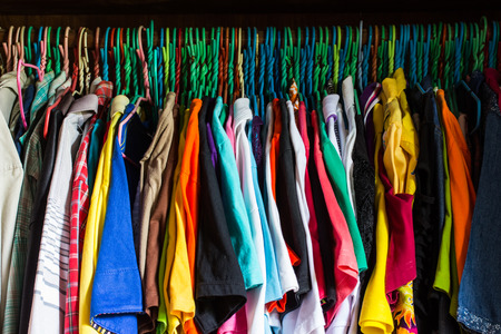 messy clothes: messy closet overfilled with colorful woman clothes on hangers and stuffed in any available space