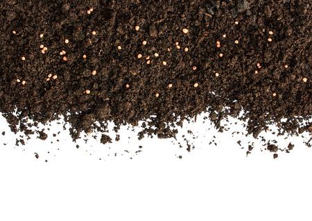 黒い土と化学肥料が白い背景のヒープ