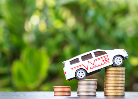 ambulance on coin on wooden background. Concept for finance health check or cost of business Stock Photo