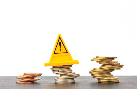 Risky coin stack and Warning label on white background.Financial crisis concept. Stock Photo