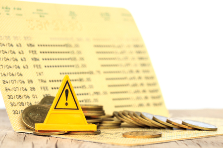 Bank statement with  Coins falling and Warning label Stock Photo