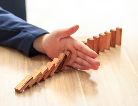 businessman hand stop dominoes continuous toppled.