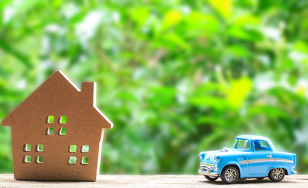 Paper house and toy car on wood and nuture background.