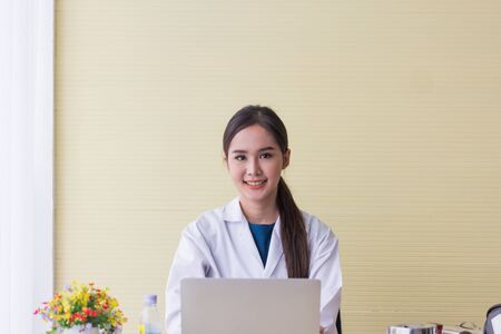 Asian female doctor smiled sweetly sitting on the desk with a notebook in the office. Stock Photo