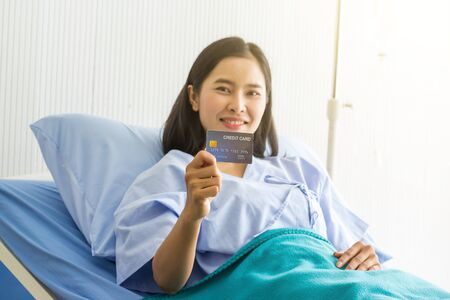Young Asian female patient holding credit card and smiling. Stock Photo