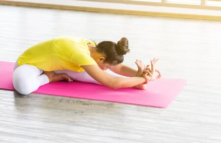 Asian female yoga teacher in a yellow sport suit sitting on pink asana in the training room