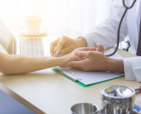 Close up of doctor hand reassuring her female patient at hospital. Closeup hands of medical doctor carefully holding patients hands. Kind doctor giving real support for patient Stock Photo