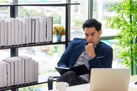 Young Asian businessmen watching the appointment book in the office Stock Photo