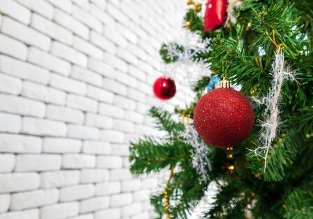 Christmas tree decorated with Red balls toys on a white wall, copy space.