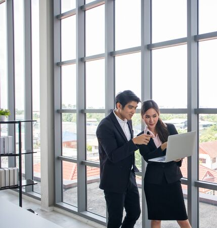 Young Asian businessmen and business women consult the work together. By looking at the notebook in the workplace Stock Photo