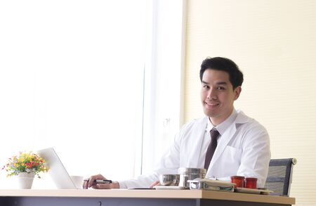 Asian young doctor is smiling on a desk with a notebook and medical equipment in the office