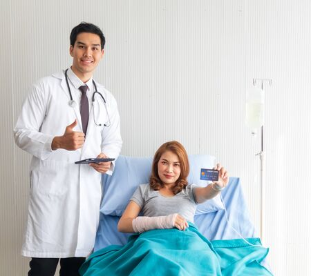The female patient in the bed carried a credit card, with a young doctor standing there to support by the bed. Stock Photo